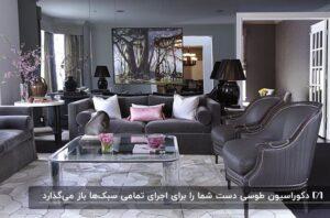 دکوراسیون طوسی نشیمن با مبلمان خاکستری، کوسن صورتی و جلو مبلی شیشه ای