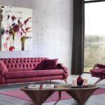 مبل چستر سرخابی با کوسن و قالیچه سرخابی در یک اتاق به رنگ طوسی