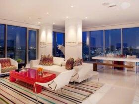 پذیرایی با دیوارهای شیشه ای، مبلمان سفید با میز جلومبلی قرمز و دکوراسیون ستون