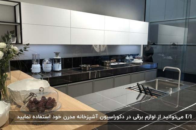 آشپزخانه مدرن با کابینت های سفید و طوسی و لوازم برقی سفید به عنوان دکوری روی کابینت