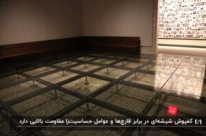 فضای یک نمایشگاه با کفپوش شیشه ای، مبلمان ال شکل به رنگ قهوه ای تیره
