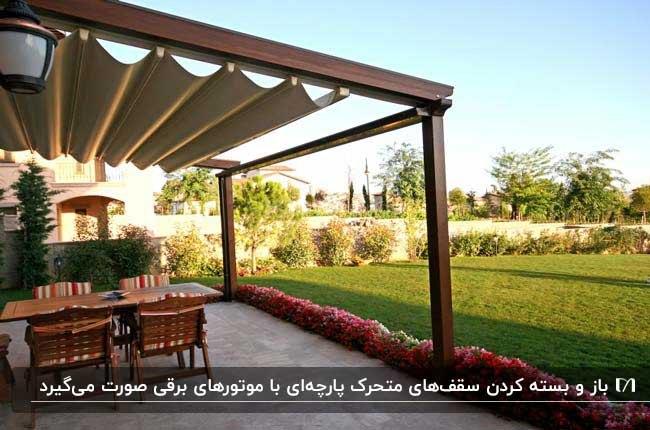 سقف متحرک پارچه ای کرم رنگ با پایه های چوبی در حیاط خانه به همراه میز و صندلی های چوبی