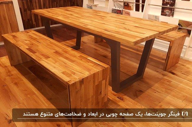 میز غذاخوری چوبی با پایه فلزی و دو نیمکت از نوع فینگر جوینت