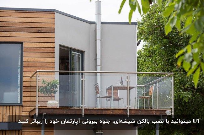 نمای ترکیبی خانه ای با چوب و سیمان و بالکن شیشهای و میز و صندلی های چوبی و فلزی