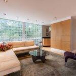 نشیمنی با مبل ال شکل کرم رنگ، صندلی بادمجانی، فرش طوسی و دیوار بلوک شیشه ای