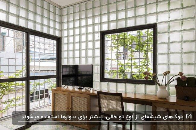 اتاقی با میز چوبی، تلویزیون و دیواری با بلوک شیشه ای