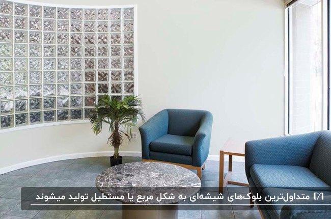 سالن انتظاری با مبل فریم چوبی و پارچه آبی و دیواری با بلوک شیشه ای