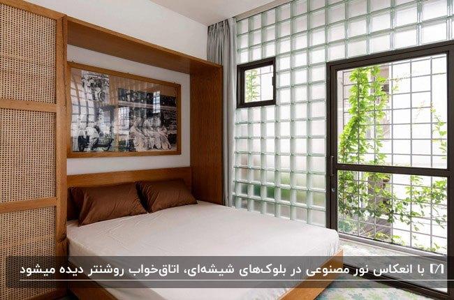 اتاق خوابی با تخت دو نفره تاشو با قاب چوبی قهوه ای و دیوار بلوک شیشه ای