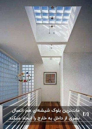 راهروی طبقه دوم خانه ای با کفپوش پارکت و دیوار و سقف بلوک شیشه ای