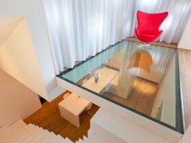 طبقه دوم خانه دوبلکسی با کفپوش شیشه ای، پرده های سفید و صندلی تاشوی راحتی قرمز رنگ