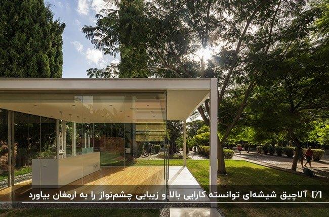 تصویر یک آلاچیق شیشه ای با اسکلت سفید در فضای باز خانه