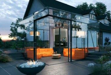 یک آلاچیق شیشه ای با مبلمان راحتی نارنجی در حیاط خانه های ویلایی کنار گودال آتش