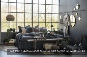 دکوراسیون طوسی یک اتاق خواب با تخت دو نفره، تعدادی بالشت و پا تختی چوبی