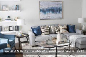 دکوراسیون طوسی همراه با جزییات آبی رنگ در تابلو و کوسن های روی مبل