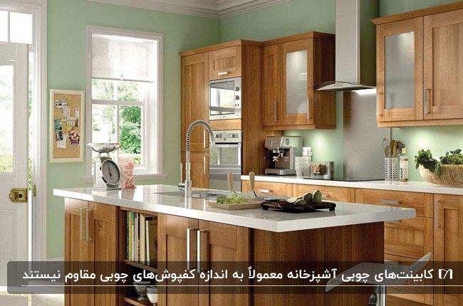 آشپزخانه ای با دیوارهای سبز کمرنگ و چوب کابینت قهوه ای رگه دار