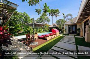 حیاط یک باغ ویلا با منظره جنگل و چند صندلی قرمز رنگ و یک چتر سایبان