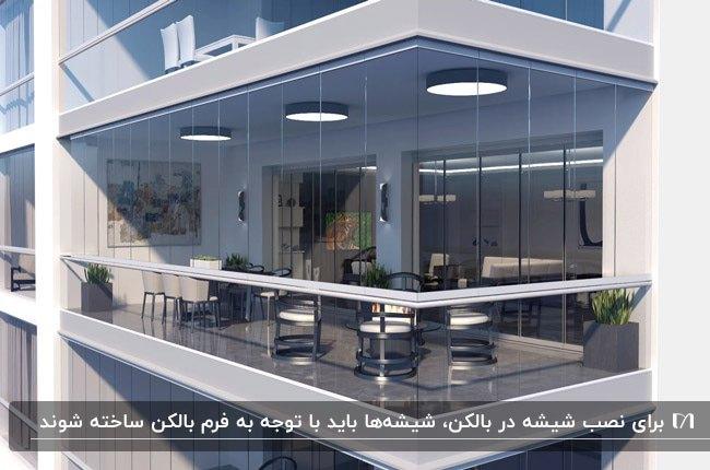 بالکن شیشهای مشتطیل شکلی با سه لوستر سقفی گرد و مبلمان و میز وصندلی غذاخوری