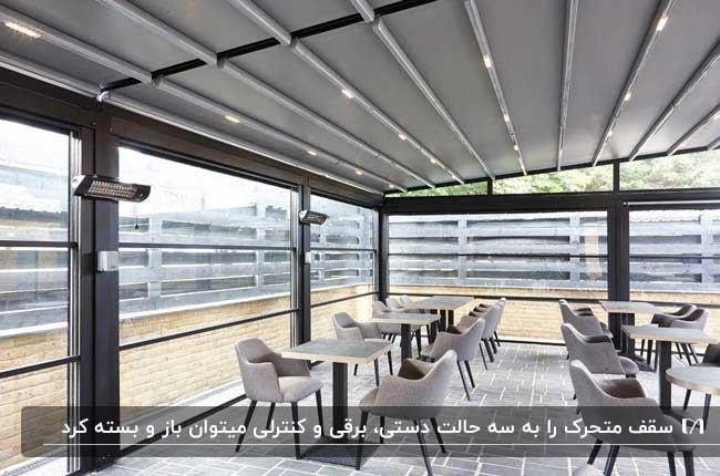 کافه شیشه ای با میزهای مربعی و صندلی های طوسی به همراه سقف متحرک