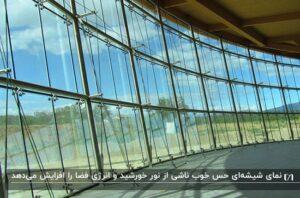فضای داخلی یک ساختمان با نمای شیشه ای که نور خورشید به خوبی در آن پخش شده با منظره ی درخت و آسمان