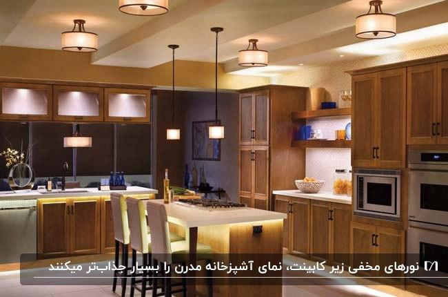 آشپزخانه مدرن با کابینت های چوبی قهوه ای و نورپردازی های مخفی و لوستری