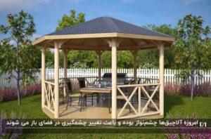 آلاچیق فلزی با نمای چوبی، نرده های ضربدری و میز و صندلی چهار نفره در فضای باز