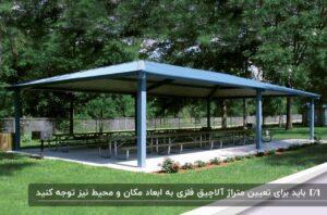 آلاچیق فلزی مستطیلی با ابعاد بزرگ به همراه یک میز و نیمکت بلند در فضای باز