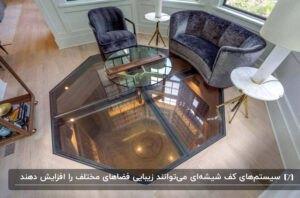 اتاقی با مبلمان مخمل زغالی، میز عسلی گرد و کفپوش ترکیبی شیشه و پارکت