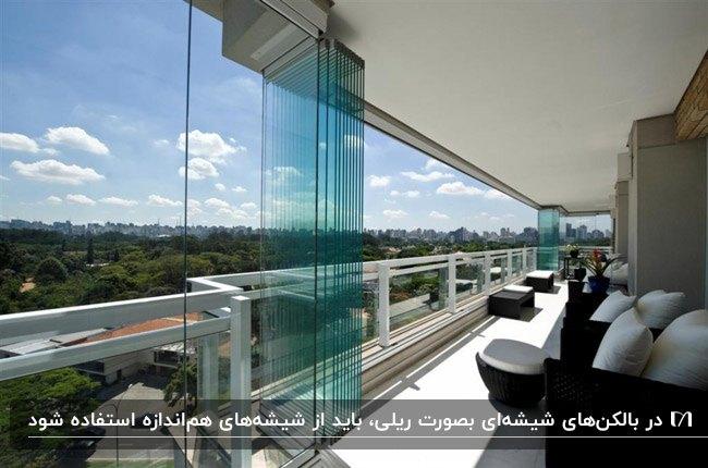 تصویر یک بالکن شیشهای با مبلمان قهوه ای و پارچه سفید و شیشه ریلی