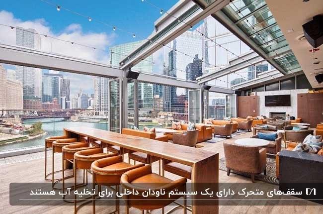 رستورانی شیشه ای با سقف متحرک و مبلمان و صندلی های قهوه ای و میزهای چوبی