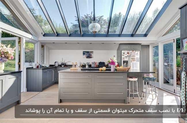 آشپزخانه مدرنی با کابینت های طوسی و سقف متحرک شیشه ای