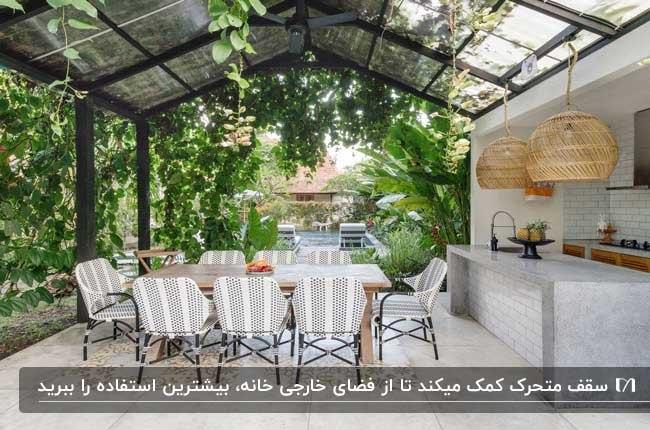 سقف متحرک با فریم مشکی در فضای باز حیاط با میز چوبی و صندلی های فلزی با پارچه راه راه