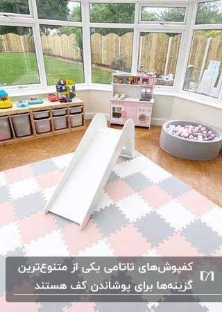 اتاق بازی کودک با پنجره های بزرگ، سرسره سفید و کفپوش تاتامی سفید و صورتی و طوسی