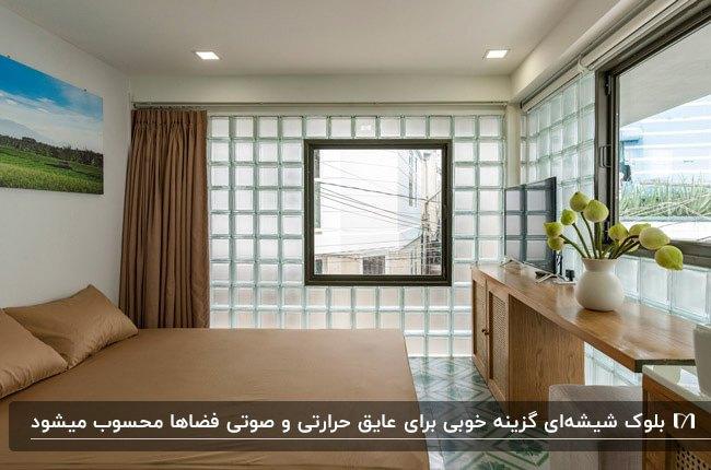 اتاق خوابی با تخت دو نفره، میز چوبی و دیوار بلوک شیشه ای