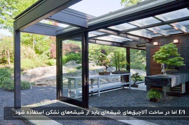 آلاچیق شیشه ای با اشکلت مشکی و شیشه های نشکن و میز سنگی
