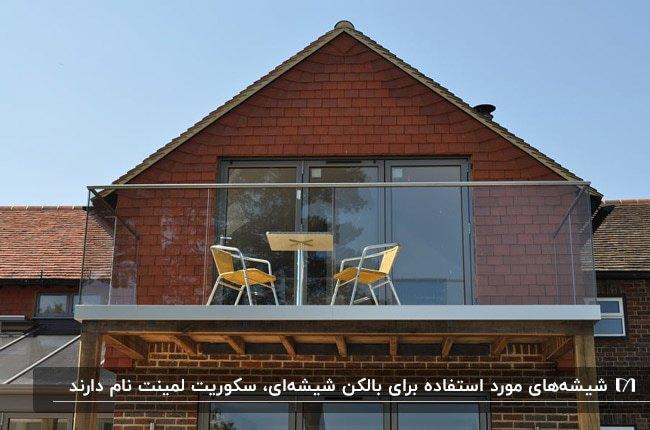 خانه ای با نمای آجر قرمز، بالکن شیشهای و میز و دو صندلی تاشوی خردلی