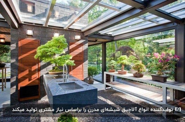 آلاچیق شیشه ای با دیوار داخلی آجری و چوبی، سینک ظرفشویی و گلدان های گل