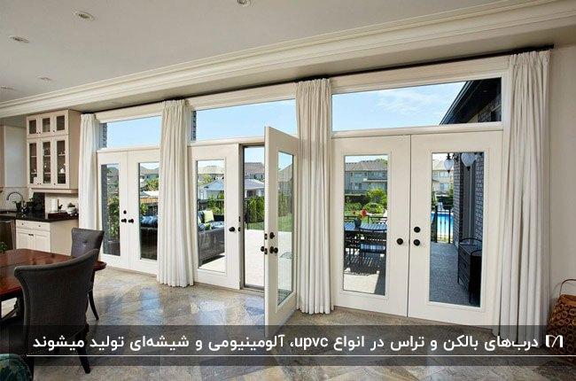 تراس بزرگی با درب های آینه ای با فریم سفید و میز و صندلی های قهوه ای