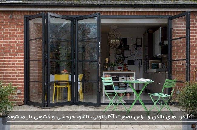 نمای آجر قرمز خانه ای با درب تراس تاشوی فریم مشکی و میز و صندلی های تاشو فلزی سبز رنگ