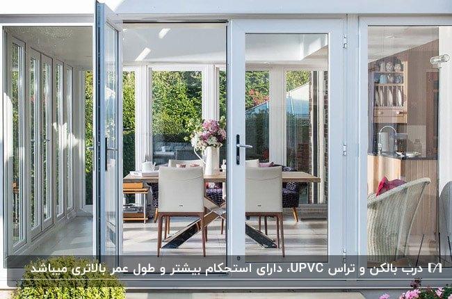 تراسی با درب یوپیویسی فریم سفید، میز و صندلی های غذاخوری چوبی و با پارچه کرم رنگ