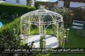 آلاچیق فلزی سفید با میله های نازک و ظریف و طراحی گنبدی و کلاسیک در باغچه