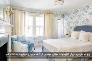 دکوراسیون اتاق خواب سنتی با تم آبی و سفید با یک تخت، یک مبل و کاٰغذ دیواری گلدار