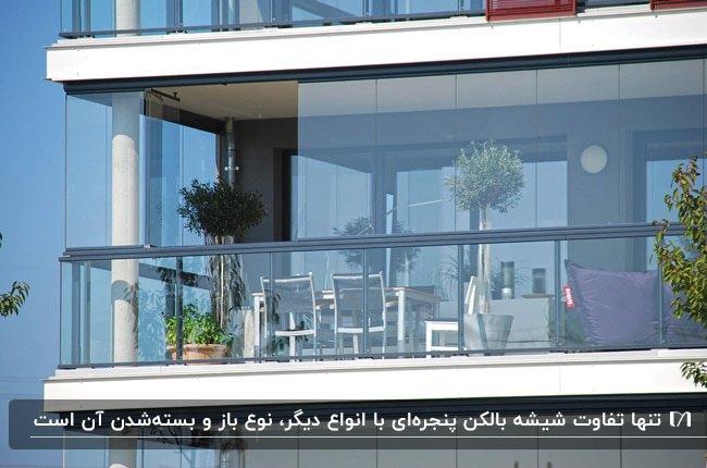 تصویر یک بالکن شیشهای با شیشه های پنجره ای، گلدان های گل و مبلمان