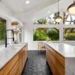 آشپزخانه مدرن با سقف شیب دار و کابینت ترکیبی سفید و چوبی به همراه لوسترهای آویز