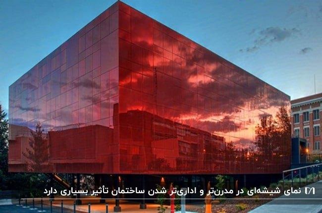 ساختمانی با نمای شیشه ای به رنگ قرمز و پیاده روی نارنجی اطراف ساختمان