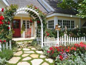 استفاده از سنگ لاشه هایی با رنگ روشن برای کفپوش محوطه ورودی یک خانه با نرده های سفید و گل های قرمز