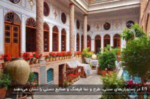 نمای رستوران سنتی ایرانی با درها و پنجره های سنتی و گلدان های شمعدانی چیده شده در ایوان رستوران
