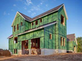 عایق کاری نمای یک ساختمان در حال ساخت سبز رنگ با پنجره های نصب نشده