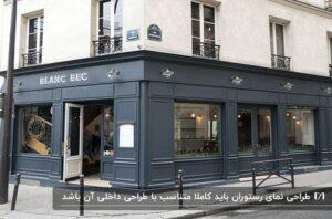 نمای فلزی یک رستوران به رنگ خاکستری کنار پیاده رو و ساختمانهای سفید رنگ