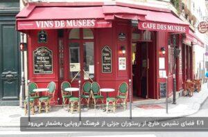 نمای روستوران به رنگ قرمز با سایبان هایی قرمز رنگ و چند میز سفید و صندلی های سبز