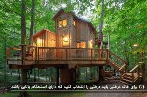 یک خانه درختی چوبی با چراغ های روشن و یک ایوان به همراه حفاظ دور تا دور آن